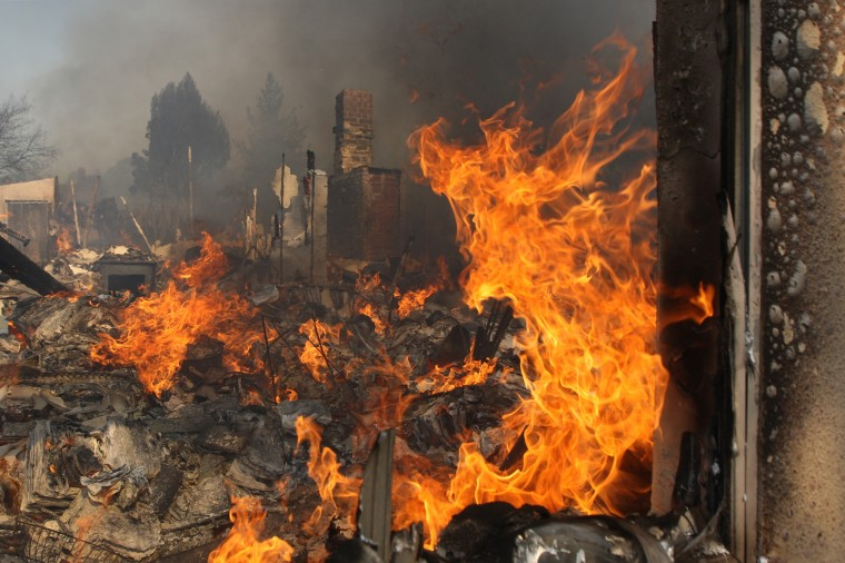 SAN MARCOS, CA - MAY 15: A house burns at the Cocos fire on May 15, 2014 in San Marcos, California. Fire agencies throughout the state are scrambling to prepare for what is expected to be a dangerous year of wildfires in this third year of extreme drought in California. (Photo by David McNew/Getty Images)