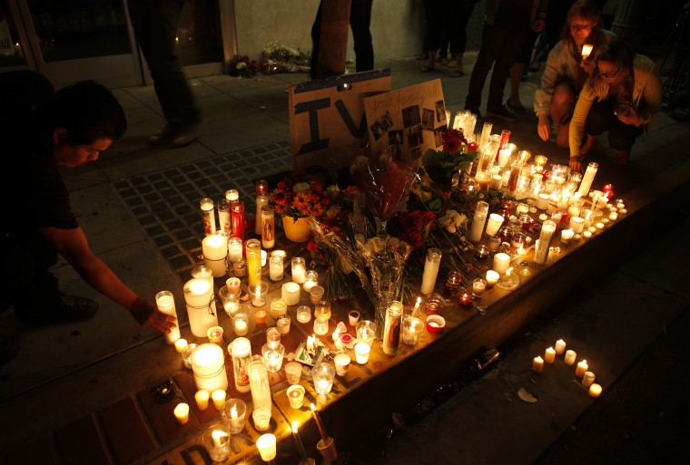 People leave candles and flowers at a growing memorial in front of the IV Deli Mart on Pardall Road in Isla Vista on May 24, 2014 in Santa Barbara, California. A man was shot and killed at the store in Friday night's rampage, one of the several crime scenes. A mentally disturbed 22-year-old man sprayed bullets from his car in the Southern California college town of Isla Vista, killing six people. (Spencer Weiner/Getty Images)