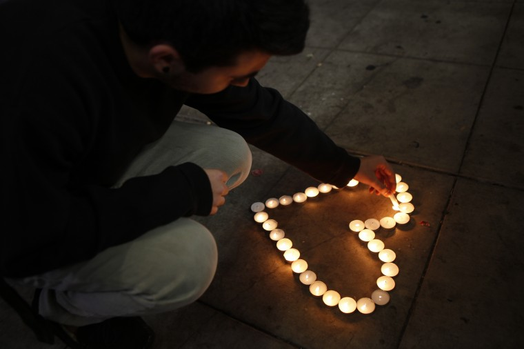 UC Santa Barbara student Eldar Erlich, 20, lights candles at a growing memorial in front of the IV Deli Mart on Pardall Road in Isla Vista on May 24, 2014 in Santa Barbara, California. (Spencer Weiner/Getty Images)