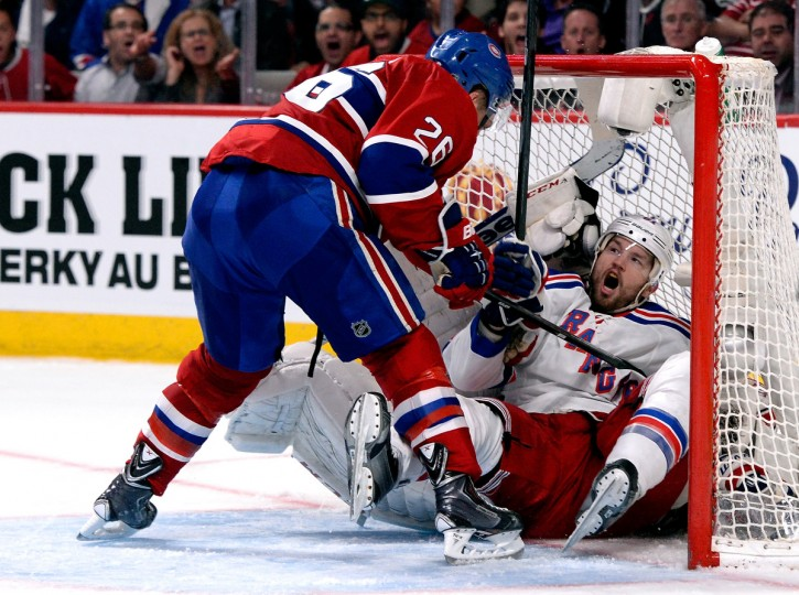 Rick Nash #61 of the New York Rangers crashes into Dustin Tokarski #35 of the Montreal Canadiens during Game Five of the Eastern Conference Final in the 2014 NHL Stanley Cup Playoffs at Bell Centre in Montreal, Canada. (Richard Wolowicz/Getty Images)