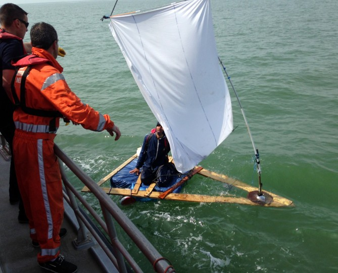 "French coast rescuers support a 23-year-old Afghan trying to cross the Channel on a makeshift raft using a bedsheet as a sail off Sangatte. The man, who had started developing hypothermia, ""was first disappointed and then glad at being rescued,"" said Bernard Barron, the head of the coast rescue service in Calais. (Getty Images)"