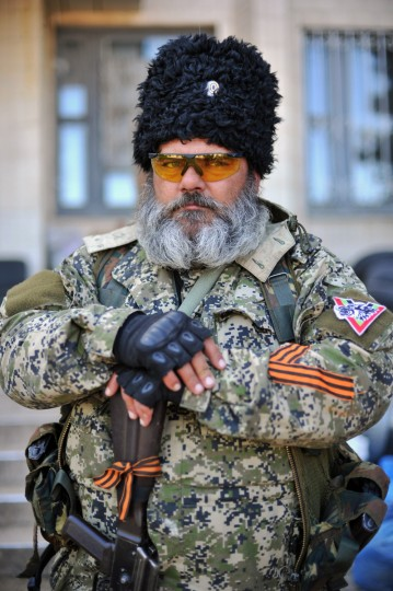 A pro-Russian militant holds a Kalashnikov as he guards a barricade outside the city hall in downtown Kramatorsk, eastern Ukraine a day after heavy fightings between pro-Russian militiants and Ukranian troops killed at least 34 people near the eastern Ukranian city of Slavyansk. The death toll from a military offensive in a flashpoint town in east Ukraine rose to at least 34, officials said on May 6, amid fresh warnings of civil war and the shutdown of a major airport in the region. (Genya Savilov/Getty Images)