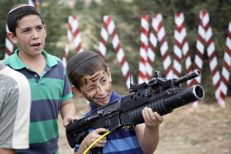 An Israeli boy plays with an M-16 rifle during a traditional military weapon display to mark the 66th anniversary of Israel's Independence at the West Bank settlement of Efrat near the biblical city of Bethlehem. Israelis are marking Independence Day, celebrating the 66th year since the founding of the Jewish State in 1948 according to the Jewish calendar. (Gali Tibbon/Getty Images)