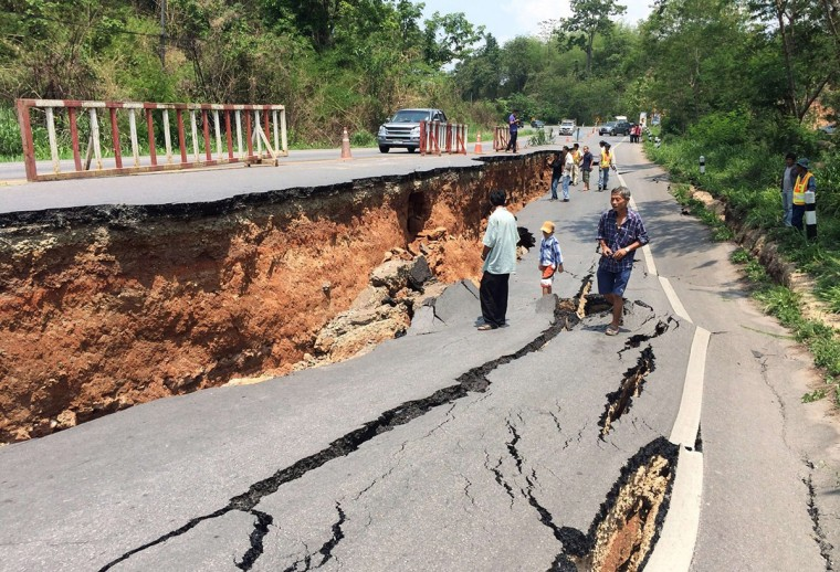 People walk past cracks on a highway a day after a 6.0-magnitude quake struck in Thailand's northern province of Chiang Rai. An elderly woman died and 23 other people were injured after a strong earthquake shook northern Thailand, an official said on May 6, as aftershocks continued to rattle the mountainous region popular with tourists. (Getty Images)
