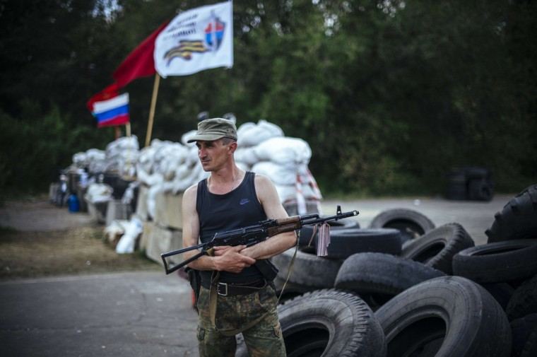 """An armed pro-Russian militant stands guard at a barricade outside the village of Shchastya near the eastern Ukrainian city of Lugansk. Ukraine launches Western-sponsored roundtable """"national unity"""" talks on Wednesday but without pro-Moscow rebels who are waging an armed insurgency in the east that threatens to tear the country apart. (Dimitar Dilkoff/Getty Images)"""