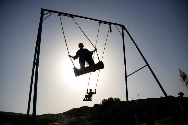 Afghan youth play on swings on the outskirts of Mazar-i-sharif. Afghanistan remains at war, with civilians among the hardest hit, as the Taliban(Farshad Usyan/Getty Images)