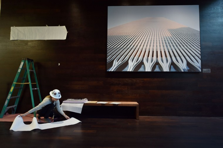 A worker under a photograph of the World Trade Center seen during a press preview of the National September 11 Memorial Museum at the World Trade Center site May 14, 2014 in New York. (Stan Honda/Getty Images)