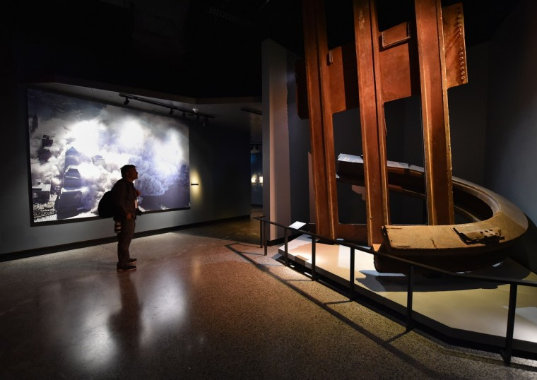 A photograph of the World Trade Center after the September 11, 2001 attacks (L) and a column and facade segment (R) seen during a press preview of the National September 11 Memorial Museum at the World Trade Center site May 14, 2014 in New York. (Stan Honda/Getty Images)