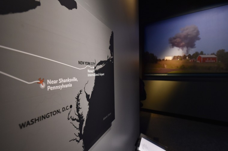 An exhibit about the plane that crashed near Shanksville, Pennsylvania on September 11, 2001 and a photograph of the plane crash (R), seen during a press preview of the National September 11 Memorial Museum at the World Trade Center site. (Stan Honda/Getty Images)