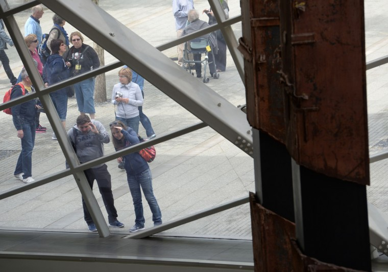 """People peer in at the World Trade Center """"tridents"""" (R), two steel columns that formed part of the building's structural support, seen in the National September 11 Memorial Museum at the World Trade Center site. (Stan Honda/Getty Images)"""