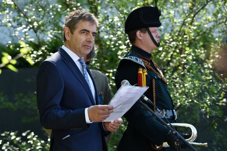 "British actor and comedian Rowan Atkinson (L) reads a poem by First World War poet Wilfred Owen, while visiting ""No Man's Land: The Soldiers' Charity Garden"" at the Chelsea Flower Show in west London, on May 19, 2014. The Chelsea flower show, held annually in the grounds of the Royal Hospital Chelsea, will run this year from May 20-24. (Leon Neal/Getty Images)"