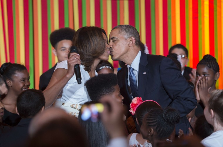 US President Barack Obama (R) kisses First Lady Michelle Obama as he makes a surprise visit to the White House Talent Show, an event sponsored by The President's Committee on the Arts and the Humanities (PCAH), at the White House in Washington, DC. (Jim Watson/Getty Images)