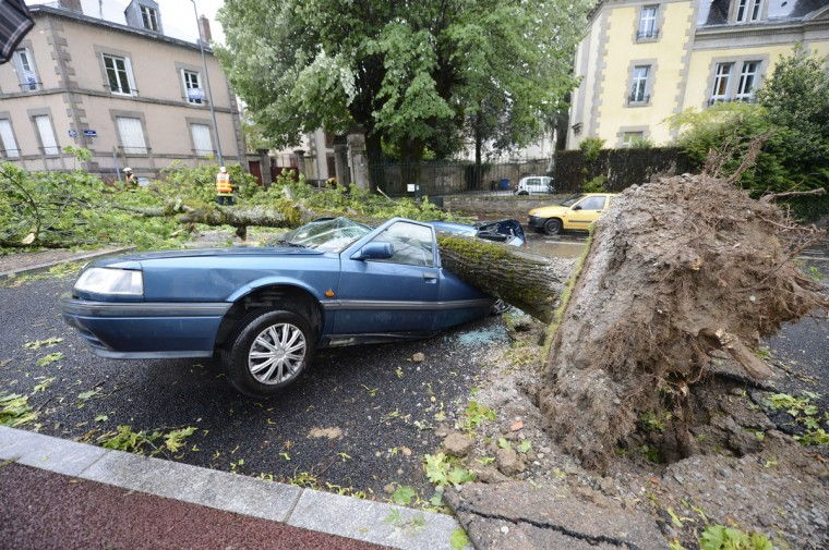 An emergency response worker cuts a tree which fell onto a car during a storm and strong winds, in Limoges. High winds up to 120 km/h and storms have caused at least one death and cut off some 42 000 homes from electricity today in the Midi-Pyrenees region of France. (Pascal Lachenaud/Getty Images)