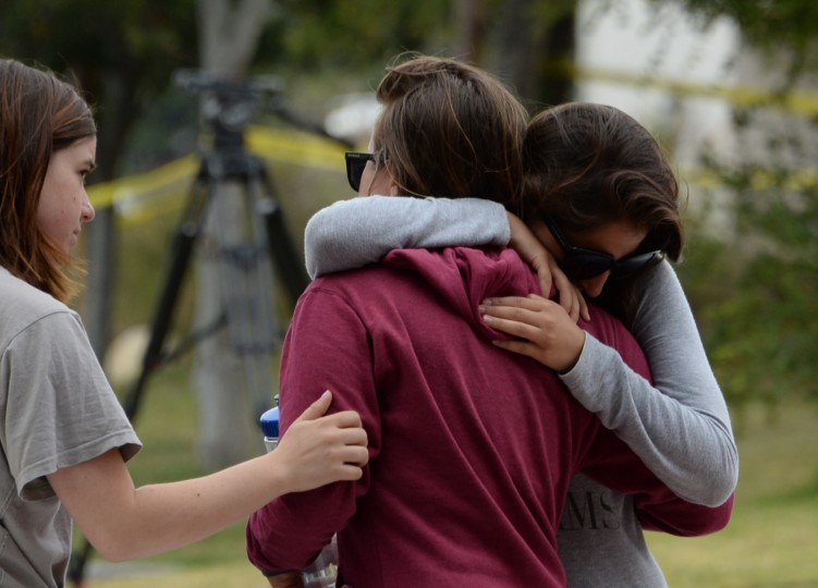 Students hug on May 24, 2014, after a drive-by shooting in Isla Vista, California, a beach community next to the University of California Santa Barbara. Seven people, including the gunman, were killed and seven others wounded in the May 23 mass shooting, Santa Barbara County Sheriff Bill Brown said Saturday. (Robyn Beck/AFP/Getty Images)