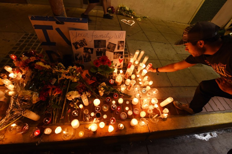 A student lights a candle at a makeshift memorial outside the IV Deli Mart where one of the victims of a killing spree was shot and killed near the University of California, Santa Barbara campus during a candlelight vigil for those affected by the tragedy in Isla Vista on May 24, 2014 in Santa Barbara, California. (Robyn Beck/AFP/Getty Images)
