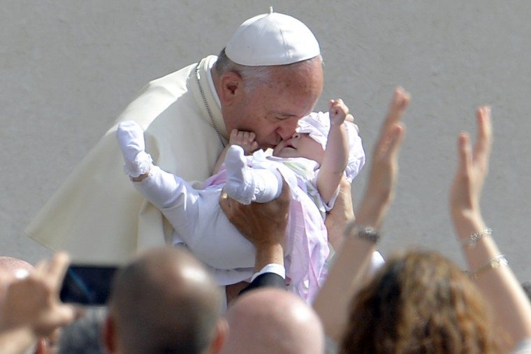 Pope Francis kisses a baby as he arrives for his general audience at St Peter's Square at the Vatican. (Andreas Solaro/Getty Images)