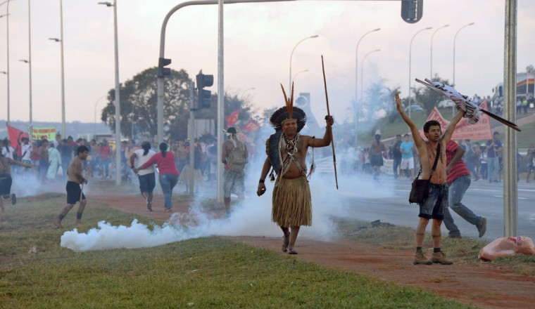 An indigenous man protests against the upcoming FIFA World Cup in Brasilia. Police in the Brazilian capital fired tear gas Tuesday to break up a protest by Indian chiefs and groups opposed to the money being spent to host the World Cup. (Evaristo Sa/Getty Images)