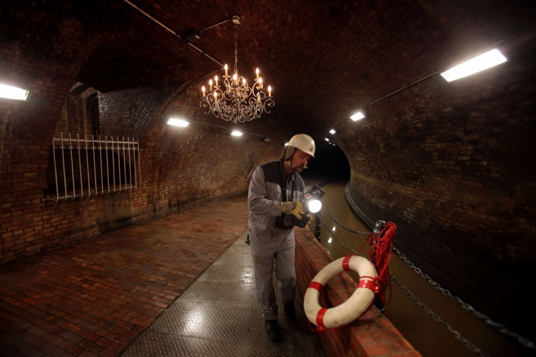 A worker of the urban drainage company walks through the so-called candelabra hall of the canalisation system of the city of Cologne, western Germany, during an inspection. When the system was inaugurated in the year 1890, the room was equipped with two candelabras, as the then German Emperor William II was expected to visit. (oliver Berg/Getty Images)