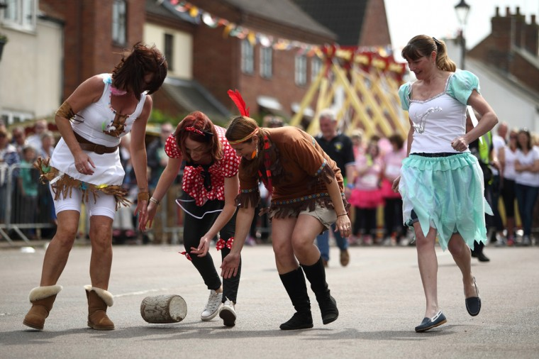 A team roll a wooden 'cheese' during the Stilton Village Festival cheese rolling competition on May 5, 2014 in Stilton, England. The Stilton annual cheese rolling competition, which is held annually on every May Day Bank Holiday involves teams of four competing against each other by rolling cheese down the High Street to be crowned the 'Stilton Cheese Rolling Champions'. (Jordan Mansfield/Getty Images)
