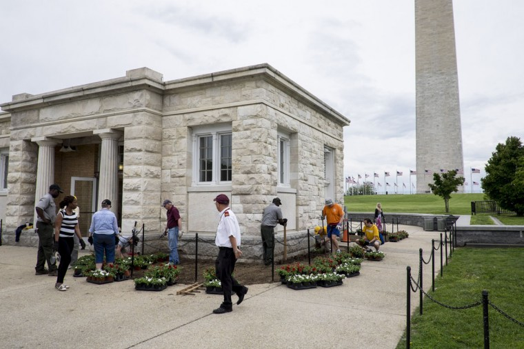 Workers prepare the landscaping around the Washington Monument visitor's center. (Photo by Pete Marovich/Getty Images)