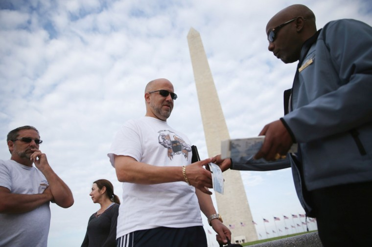 William Davenport, right, an employee of Eastern National, which runs the bookstore of the Washington Monument, hands out tickets to visitors May 12, 2014. (Photo by Alex Wong/Getty Images)