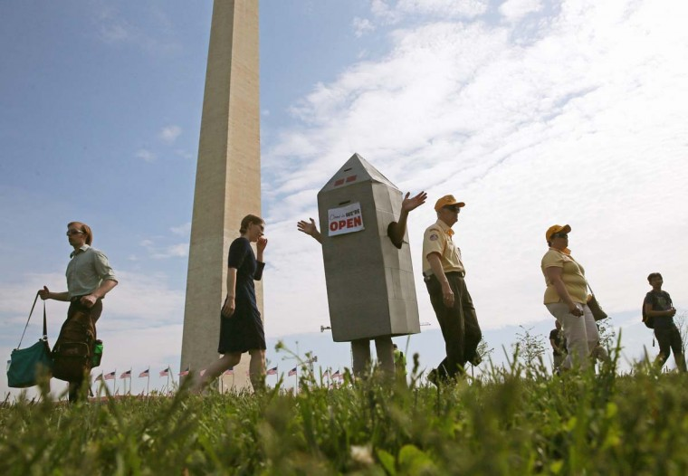 Steven Avilla wears a Washington monument costume as he greets visitors to the monument, May 12, 2014 on the ground of the monument in Washington, DC. The Washington Monument was reopened after it has been closed for a restoration due to damage caused by a 5.8-magnitude earthquake that struck the Washington, DC area on August 23, 2011 (Mark Wilson/Getty Images)