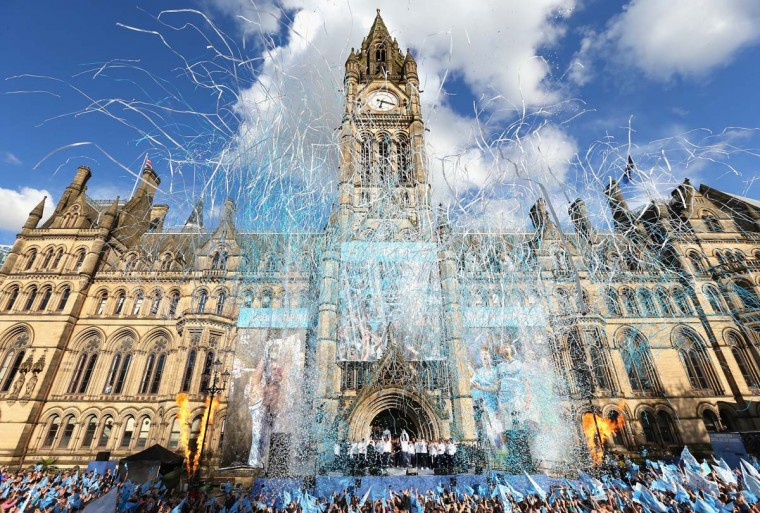 Vincent Kompany of Manchester City lifts the Barclays Premier League trophy aloft outside Manchester Town Hall at the start of the Manchester City victory parade around the streets of Manchester on May 12, 2014 in Manchester, England. (Alex Livesey/Getty Images)