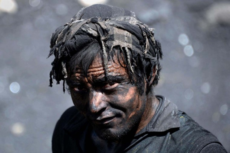 An Afghan miner poses for a photograph as he works at a coal mine which collapsed on April 30 killing some 40 miners and trapping an unknown number of others in the Dar-i- Suf district of Samangan province, some 200 kms from Mazar-e-Sharif on May 1. Officials at the site in Samangan province said an explosion inside the mine on April 30 killed some 40 miners and trapped an unknown number of others.   || CREDIT: FARSHAD USYAN - AFP/GETTY IMAGES