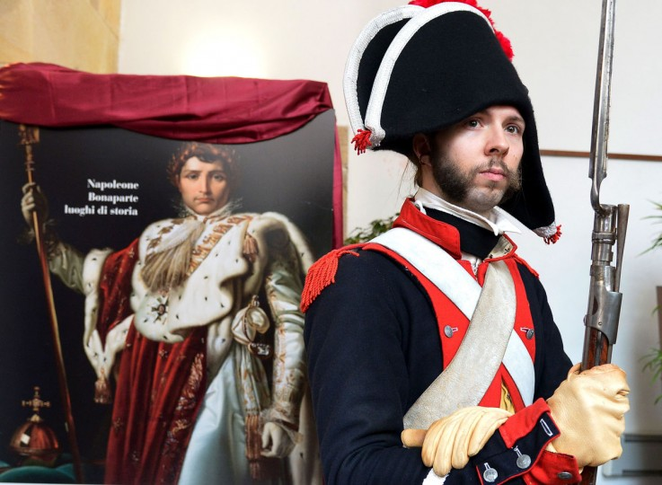 A man dressed as a Napoleonian soldier poses on May 4, 2014, next to a poster of the French Emperor in Portoferraio on the Italian island of Elba. (VINCENZO PINTO/AFP/Getty Images)