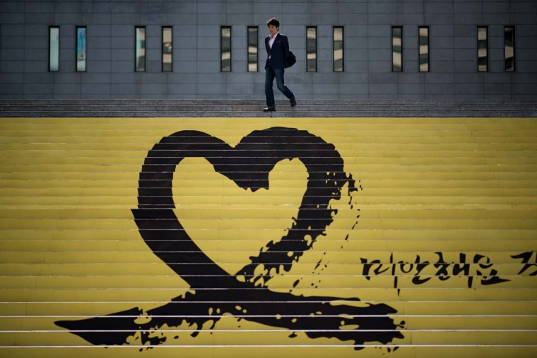 A man walks down steps past a tribute to victims of the Sewol ferry, in Seoul on May 9. The confirmed death toll stood at 273, with 31 still unaccounted for, after four more bodies were retrieved from the sunken ship overnight.  || CREDIT: ED JONES - AFP/GETTY IMAGES