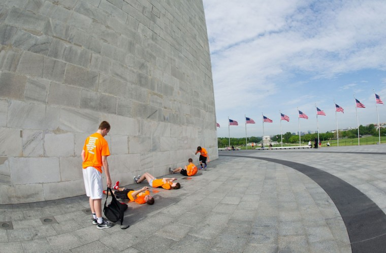 Students lie down to takes pictures at the base of the Washington Monument May 12, 2014. (KAREN BLEIER/AFP/Getty Images)