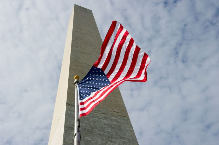 The Washington Monument is seen behind the US flag. (KAREN BLEIER/AFP/Getty Images)