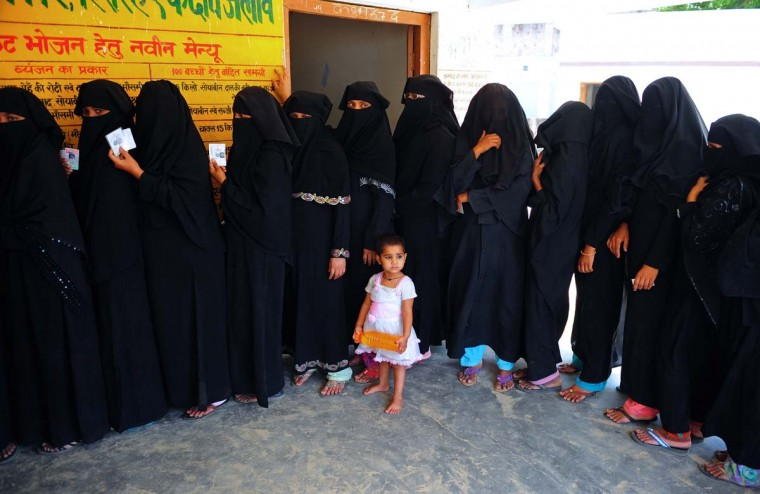 A child looks on as Indian Muslim women wait in line to cast their votes at a polling station in Azamgarh, about 275 kms from Lucknow in northern Uttar Pradesh state on May 12, 2014. Voters headed to the polls in the final stage of India's bitterly fought mammoth election that is expected to catapult Hindu nationalist hardliner Narendra Modi to power. (Sanjay Kanojia/AFP/Getty Images)
