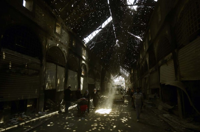 Rays of light burst through holes in the roof of Maskuf covered market as Syrians walk in the alleys on May 12, 2014 in the Old City of Homs, some 162 kilometres north of the capital Damascus. Syrians have been streaming back into the ruins of the Old City of Homs since May 10, 2014, picking through the remains of their homes and trying to come to terms with the destruction. (Joseph Eid/AFP/Getty Images)