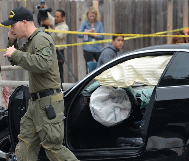 "An investigator speaks on a cell phone while inspecting a suspected gunman's car on May 24, 2014, after a drive-by shooting in Isla Vista, California, a beach community next to the University of California Santa Barbara. Seven people, including the gunman, were killed and seven others wounded in the May 23 mass shooting, Santa Barbara County Sheriff Bill Brown said Saturday. Brown said at a pre-dawn press conference that the shooting in the town of Isla Vista ""appears to be a mass murder situation."" Driving a black BMW, the suspect opened fire on pedestrians from his vehicle at several locations in the town."