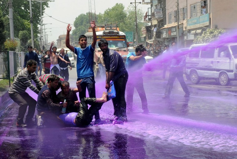 Kashmiri government employees demonstrate as riot police spray purple-dyed water cannon during a protest march in Srinagar on May 26,2014. Indian police detained dozens of government employees as they tried to stage a protest march demanding the regularisation of contractual jobs and an increase in salary. (Rouf Bhat/AFP/Getty Images)
