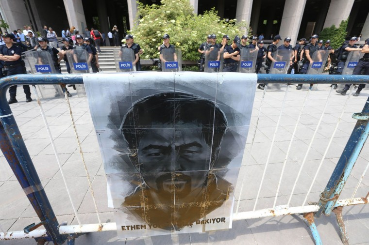 Police officers stand guard behind a printed picture of late Ethem Sarisuluk, outside the Ankara courthouse on May 26, 2014 during the trial of a riot police officer accused of killing Ethem Sarisuluk, a 26-year-old Turkish man who died during an anti-government protest last June. (Adem ALten/AFP/Getty Images)
