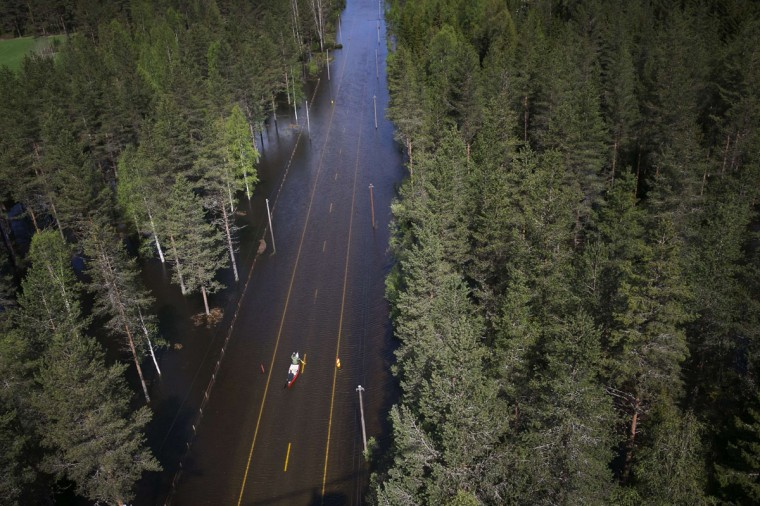 Two men paddle in a canoe on a flooded road in Trysil, southeastern Norway. Rain and melted snow have increased the water level of the river Trysilelva. (AFP/Getty Images)