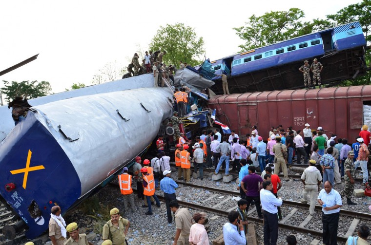 Rescue workers and mangled train compartments are pictured after the Gorakhdham Express rammed into a goods train at Chureb station in Khalilabad, some 700 kilometres (430 miles) east of New Delhi, on May 26, 2014. A passenger express train slammed into a stationary freight train in northern India killing at least nine people May 26, as rescuers worked frantically to free those trapped inside mangled carriages, officials said. (AFP/Getty Images)