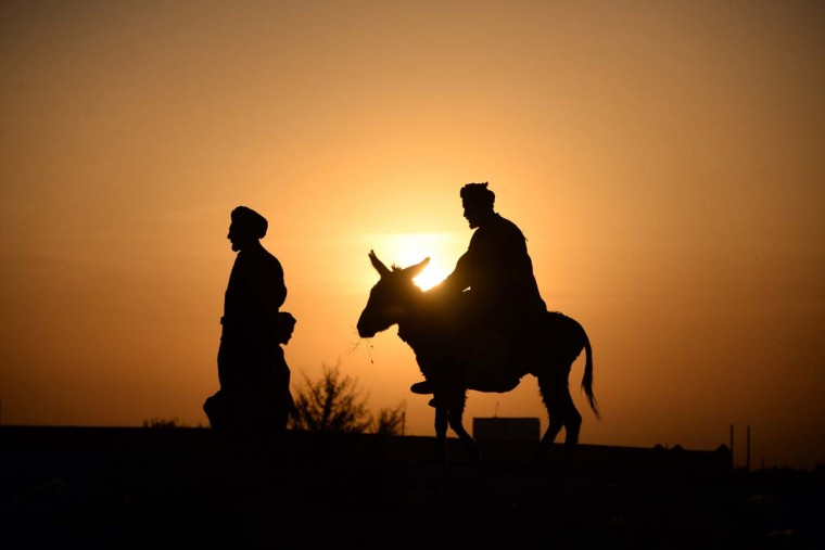 An Afghan resident rides on his donkey as the sun sets on the outskirts of Mazar-i-sharif on May 26, 2014. Afghanistan remains at war, with civilians among the hardest hit, as the Taliban wage an increasingly bloody insurgency against the government. (Farshad Usyan/AFP/Getty Images)