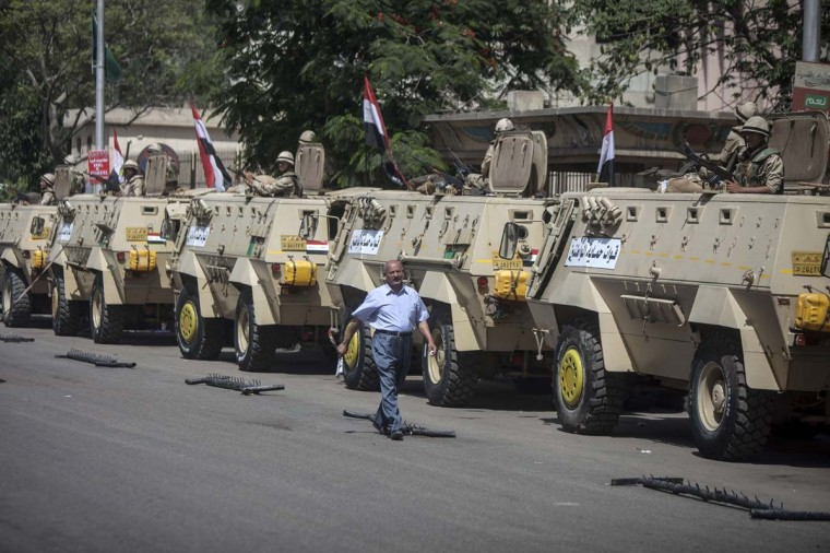 An Egyptian man walks past army vehicles stationed outside a polling station in Cairo on May 27, 2014, on the second day of Egypt's presidential election. Sisi is expected to trounce his only rival, leftist leader Hamdeen Sabbahi, in Egypt's second freely held presidential election, which is being held over two days. (Mahmoud Khaled/AFP/Getty Images)