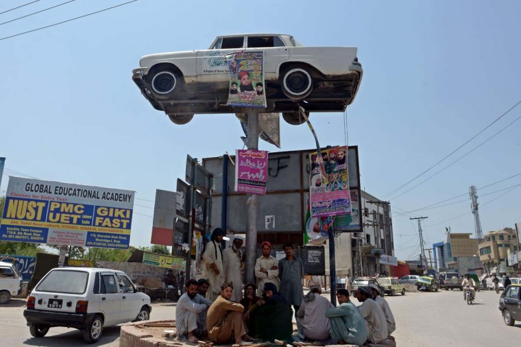 Pakistani labourers sit under the shade of a roadside installation featuring a car on a pole in Rawalpindi on May 27, 2014. Mainly hot and dry weather is expected in most parts of the Punjab province as maximum temperatures hit 40 degrees celsius. (Farooq Naeem/AFP/Getty Images)