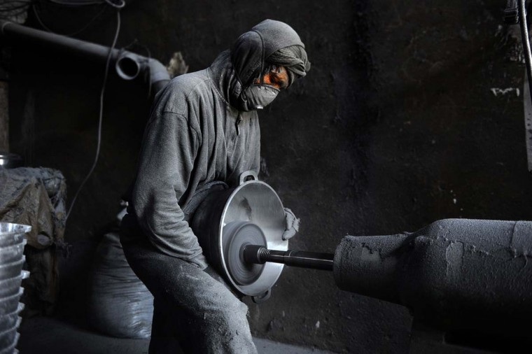 An Afghan labourer polishes a metal pot at an aluminium workshop in Herat on May 27, 2014. Some 100 people work in the Herat Aluminum factory with around around 70 to 100 tons of aluminum produced each month, with most all of its products used domestically. (Aref Karmi/AFP/Getty Images)