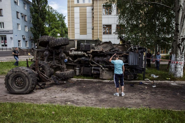 A Ukrainian man stands in front of a destroyed truck, which was previously used by pro-Russian militants and which was bombed by Ukrainian army soldiers overnight during clashes, in the eastern Ukrainian city of Donetsk, on May 27, 2014. Ukraine said today it had regained control of the airport in the eastern city of Donetsk after a day of punishing air strikes and fierce fighting with pro-Moscow separatist gunmen left dozens of people dead. (Fabio Bucciarelli/AFP/Getty Images)