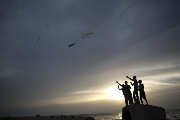 Palestinian youths hold a string connected to a kite on May 29 in Gaza City.   || CREDIT: MOHAMMED ABED - AFP/GETTY IMAGES