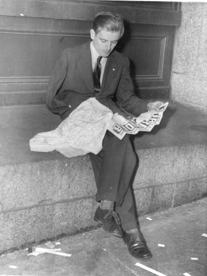 V.E. Day: Baltimore May 1945, a discharged veteran reading news of surrender while looking at a map he picked up overseas. (He would not give his name) (Baltimore Examiner and Washington Examiner)