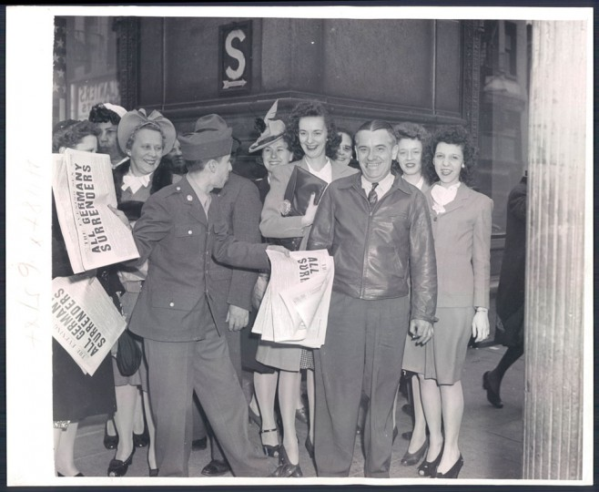 """Pvt. William Leon of New Cumberland, PA, on a fine day here jumps back into his old job of selling newspapers. Today's headline, """"ALL GERMANY SURRENDERS"""" (Photo by Sun photographer A. Aubrey Bodine.)"""