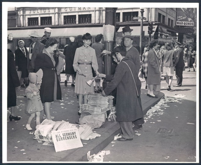 """Newspapers sold for 5 cents at Park Avenue and Lexington Street. Headline: """"All Germany Surrenders."""" (Photo by A. Aubrey Bodine/Baltimore Sun)"""