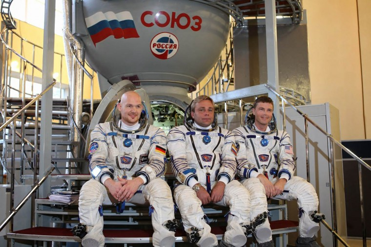 At the Gagarin Cosmonaut Training Center in Star City, Russia, Expedition 38/39 backup crewmembers Flight Engineer Alexander Gerst of the European Space Agency (left), Soyuz Commander Max Suraev (center) and NASA Flight Engineer Reid Wiseman (right) pose for pictures in front of a Soyuz simulator Oct. 18, 2013 as they participated in qualification exam simulations. They are backing up the prime crewmembers, NASA Flight Engineer Rick Mastracchio, Soyuz Commander Mikhail Tyurin and Flight Engineer Koichi Wakata of the Japan Aerospace Exploration Agency, who are scheduled to launch on Nov. 7, local time, from the Baikonur Cosmodrome in Kazakhstan on the Soyuz TMA-11M spacecraft for a six-month mission on the International Space Station. (Stephanie Stoll/NASA)