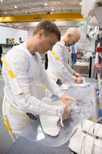 NASA astronaut Reid Wiseman (foreground) and European Space Agency astronaut Alexander Gerst, both Expedition 40/41 flight engineers, work with extravehicular activity (EVA) equipment during a training session in the Neutral Buoyancy Laboratory (NBL) near NASA's Johnson Space Center. Wiseman and Gerst are wearing the liquid cooling and ventilation garments that complement their Extravehicular Mobility Unit (EMU) spacesuits. (NASA)